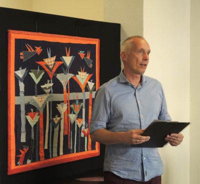Eröffnungsredner Alexander Lange, im Hintergrund  die Textilcollage »Neugierde-beidseitig« von 2012