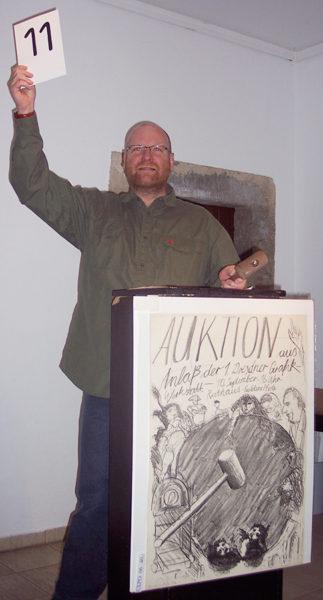 Auktionator Lars Hahn versteigert ein Plakat von Claus Weidensdorfer